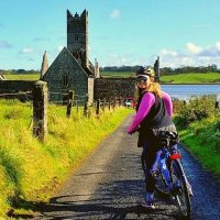 Ballina Bike Hire A cyclist on a bike tour along the Greenway Monasterieso f the Moy, Rosserk Abbey in the background